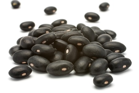 dries: A small handful of black beans - preto. Beans isolated on a white background. Close-up.