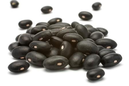 bean plant: Un peque�o pu�ado de frijoles negros - preto. Beans aislados en un fondo blanco. Close-up.  Foto de archivo