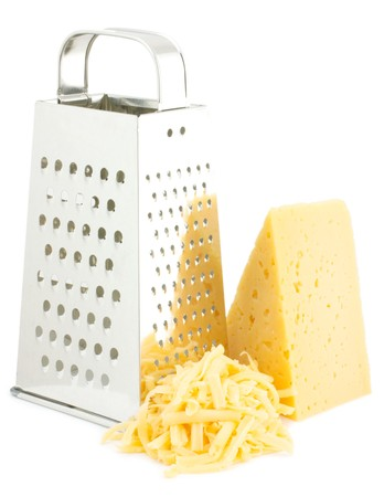 SLICER: The composition of the grated cheese. Nearby is grater and cheese. Isolated on white background. Stock Photo