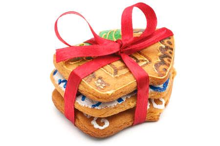 spicecake: Una pila de cookies de Navidad en la cantidad de tres piezas. Cookies en la forma de casitas. Pila hab�a atada con una cinta roja. Pintado y horneado cookies manualmente. Aislados sobre fondo blanco.