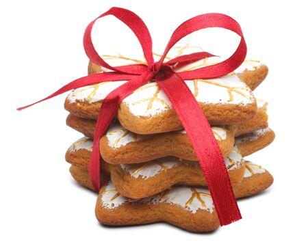 spicecake: Una pila de cuatro cookies. Las cookies hab�an atada con una cinta roja. Esto bien elaborado a mano y pintada a mano. Cookies en la forma del copo de nieve. Aislados sobre fondo blanco.