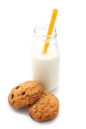 Two oatmeal cookies with peanuts and raisins. Near the glass bottle of milk and cocktail straw. Isolated on white background. photo