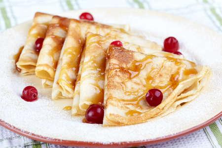maslen: Pancakes with cranberry berries and honey on a white plate