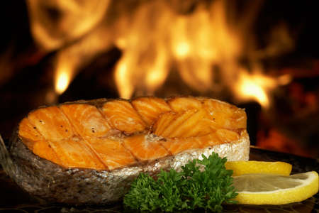 Steak salmon grilled on fire background Standard-Bild