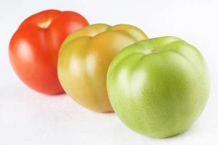 Three tomatoes of different maturity Stock Photo