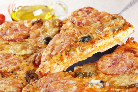 Italian cuisine. Pizza with salami, pickles and olives Stock Photo - 13429769