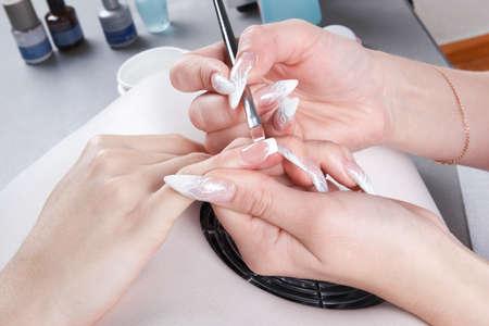 unas largas: Manicura Maestro hacer el dibujo de u�as de gel de extensi�n de blanco en el borde libre de la u�a