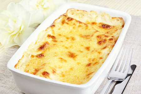 Cannelloni with chicken and mushrooms baked in sauce bechamel