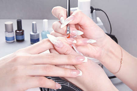 Manicure  Master make nail extension  drawing of the last layer of gel photo