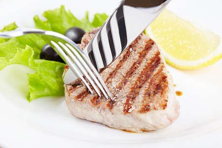 Grilled steak on white plate closeup photo