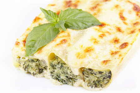 Cannelloni with spinach and ricotta baked in sauce bechamel Standard-Bild