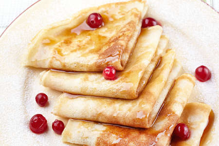 Pancakes with cranberry berries and honey on a plate Stock Photo