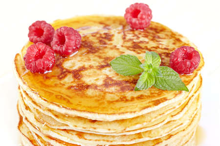 Pancakes with honey, raspberry and a mint branch photo