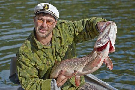 pike: Fisherman holding a big pike Stock Photo