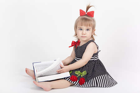 Little girl thumbs through the thick book