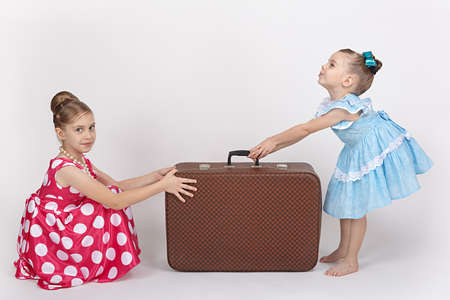 Two sisters pulled an old suitcase in different directions Stock Photo