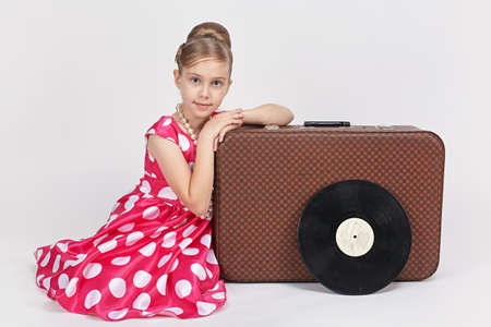Dressed in a retro style girl sitting near an old suitcase