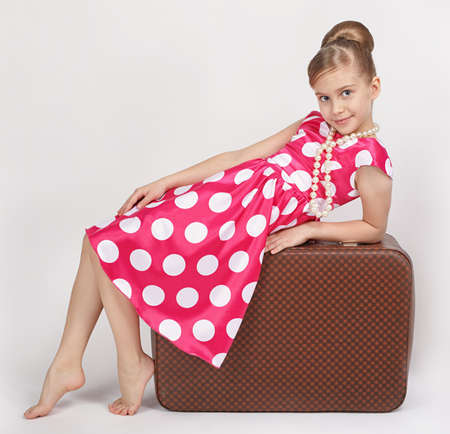 Dressed in a retro style girl sitting on old suitcase