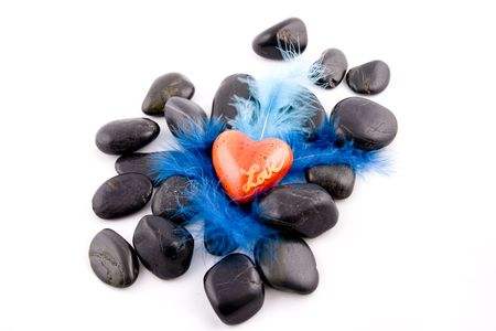 Red heart on black stones and blue plumage backrdound photo