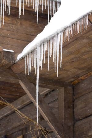 Frozen icicles on old wooden house