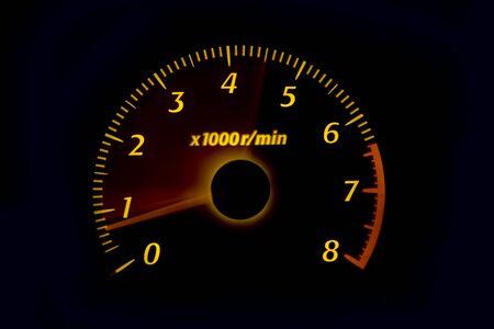 Car dashboard gauges illuminated at night, tachometer, speedometer photo