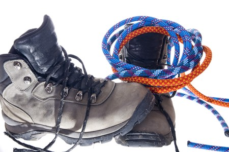 Pair of hiking boots and ropes on white background