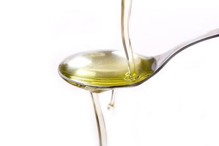 Olive oil poured  into a spoon