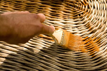 Painting willow table with protecting paint Stock Photo