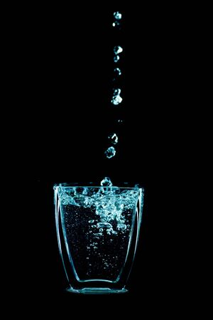 Water drops flow into glass Stock Photo