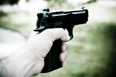 Man holds gun in his hand photo