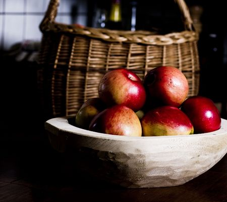 Wooden pan full of apples in kitchen