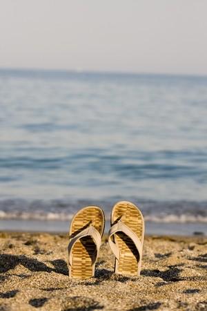 flip flop op zand strand voor de zee
