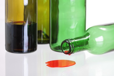 knocked over: A bottle of red wine, knocked over and dripping.  Stock Photo