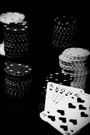 playing with money:  Casino gambling chips and playing cards  on green table Stock Photo