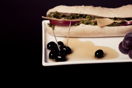 long baguette sandwich with cheese,  fresh vegetables and olives