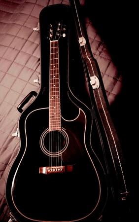black shiny acoustic guitar  in case