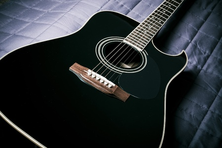black shiny acoustic guitar  on bed Stock Photo - 9405226