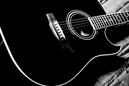 black shiny acoustic guitar  on bed Stock Photo