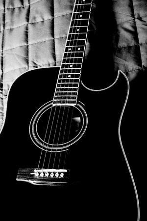 black shiny acoustic guitar  on bed Banque d'images