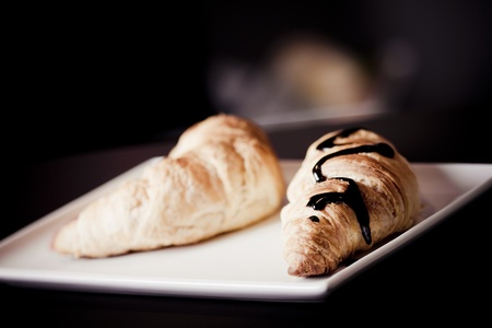 continental: Croissant with some chocolate and stwawberry sauce Stock Photo
