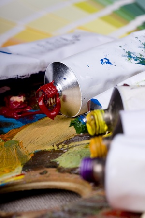 Artistic equipment: paint, brushes and knives on paint background photo