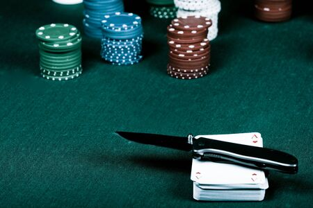 Casino gambling chips, cards and knife  on green table Stock Photo