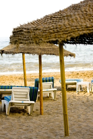Straw umbrella on the beach and chairs Stock Photo