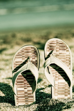 flip flop on sandy beach in front of the sea retro look Stock Photo