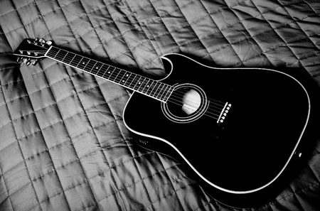 fingerboard:  black shiny acoustic guitar  on bed Stock Photo