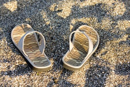 flip flop on sandy beach in front of the sea photo