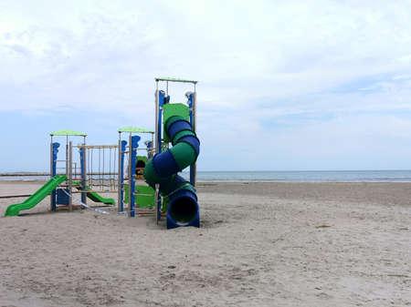 Children's slide on an empty beach during pandemic quarantine