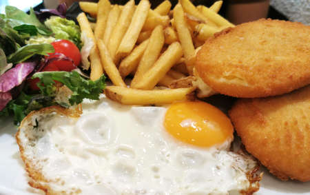 traditional Mediterranean cuisine breaded chicken with fried egg and French fries, a comprehensive lunch, main course, 版權商用圖片