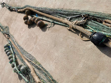 fishing nets and tackles drying on the pavement