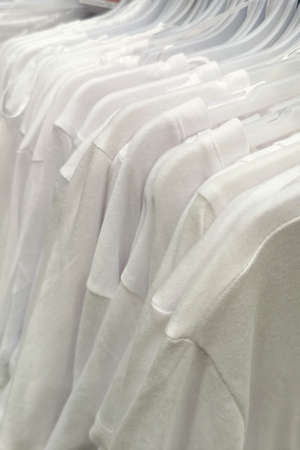 white T-shirts on hangers in the store
